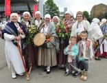 """Ozolmuižas folkloras ansamblis ''Ūzuleni"""" ar savu vadītāju Mariju Andinu."""