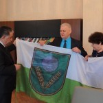 No labās: Rēzeknes novada domes priekšsēdētāja vietniece Elvīra Pizāne un pašvaldības izpilddirektors Jānis Troška pasniedz Rēzeknes novada pašvaldības karogu Agdašas pašvaldībai