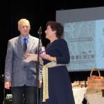Rihardam Ciblim balvu pasniedz Latgaliešu kultūras biedrības valdes priekšsēdētāja Līvija Plavinska. Foto: M. Isajeva